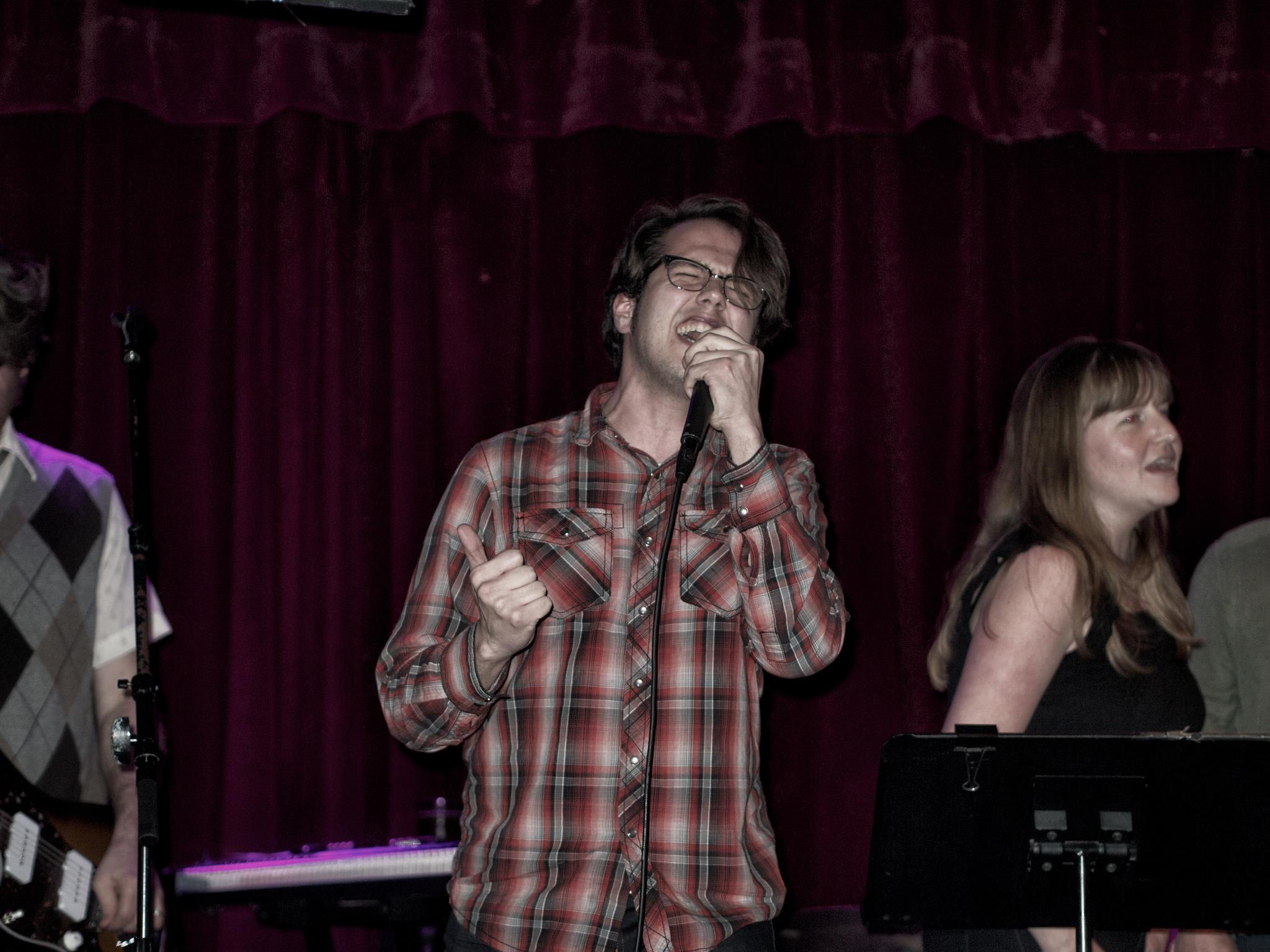 Justin belting out a song at live-band karaoke